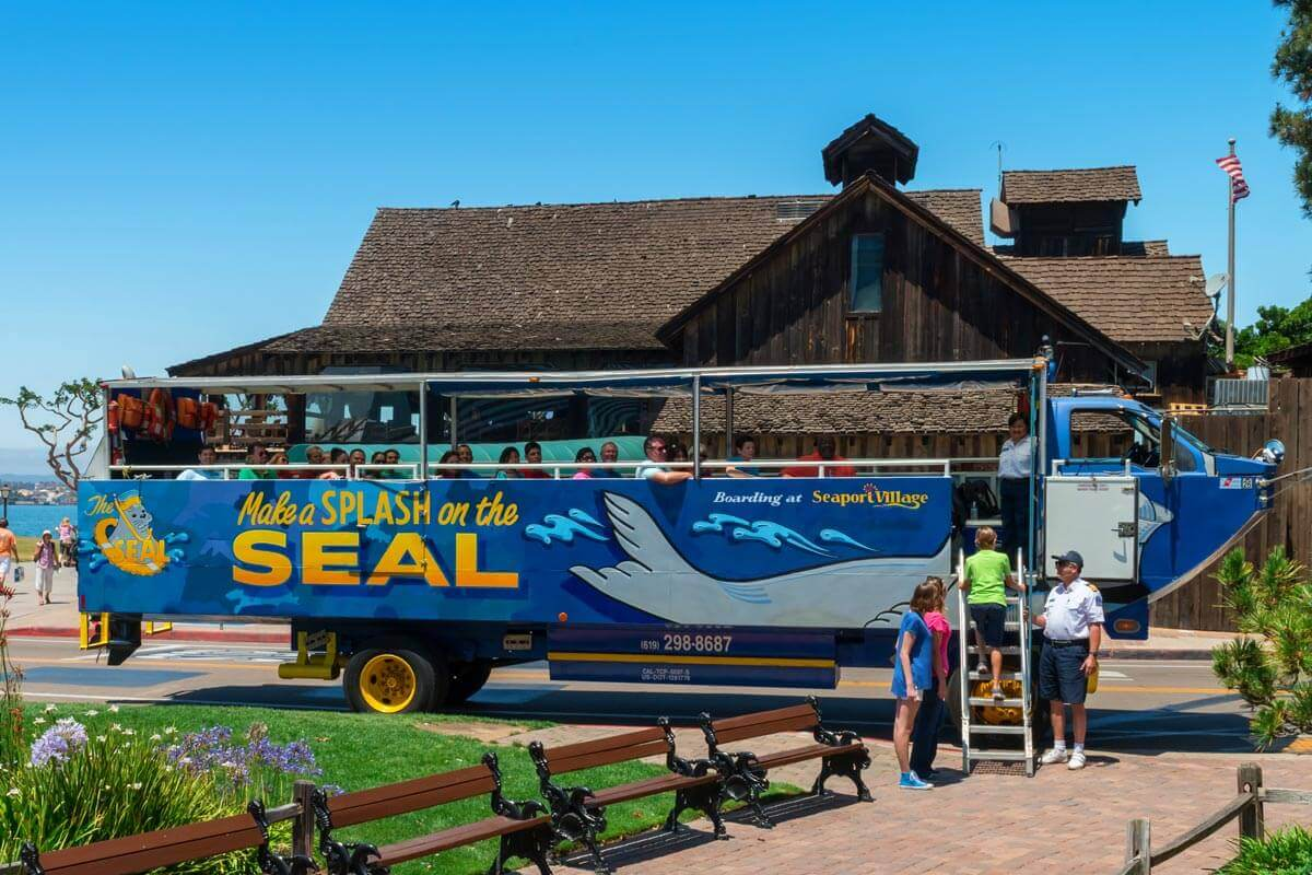 People boarding and climbing ladder of a San Diego Seal Tour vehicle at Seaport Village and being greeted by a SEAL Tour captain and guide
