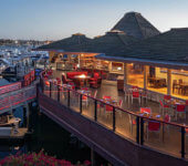 view of Hyatt Regency Mission Bay at dusk showing deck with dining tables and chairs and overlooking marina