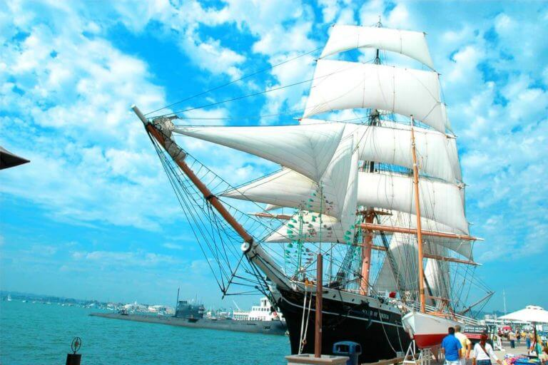 A 19th century cargo ship called the Star of India with its many sails unfurled with a complex network of ropes and pulleys against a bright blue sky in the San Diego Bay