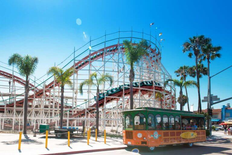 An Old Town Trolley stopped in front of the Belmont Park Rollercoaster with the coaster itself in a high-speed turn