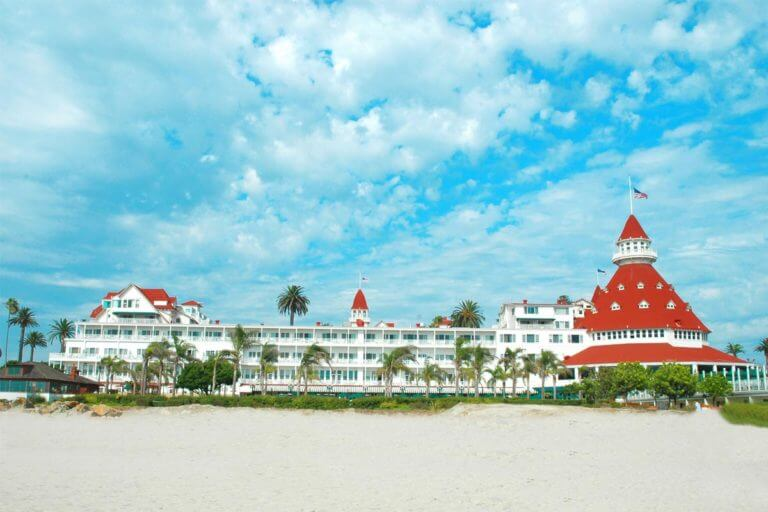 A beachside wide-angle view of the Hotel del Coronado with sand in the foreground and an arrangement of palm trees