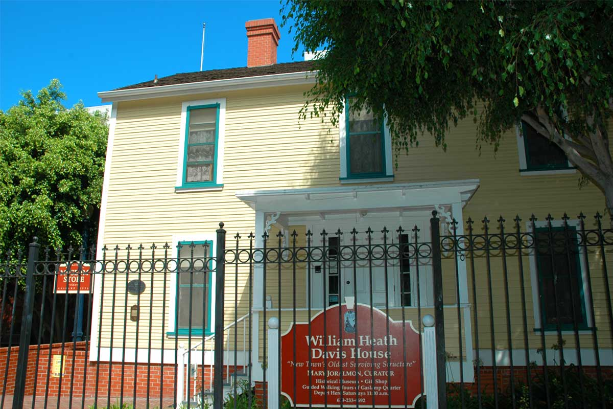 The exterior of the historic Davis-Horton House in San Diego behind a tall iron fence painted a very pale green or yellow constructed in the