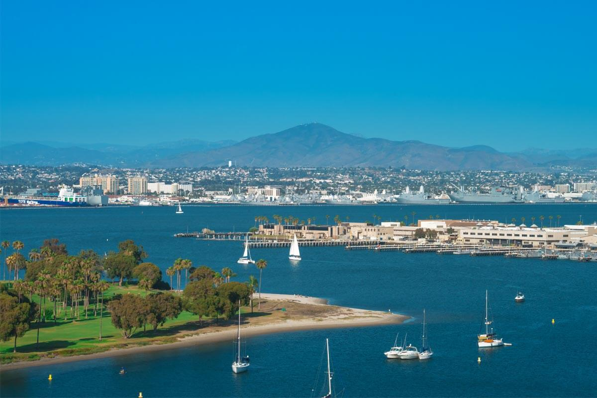 A very wide view of the Ferry Landing in San Diego where you can see a public park with a beach, a naval base, the San Diego bay with several sailboats floating around and mountains in the distance