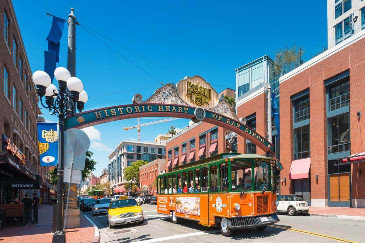 An Old Town Trolley passing underneath the arch that welcomes visitors to San Diego's Gaslamp Quarter