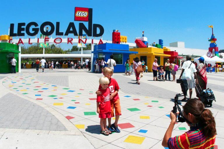 Entrance to Legoland San Diego where 2 young platinum blonde smiling boys are being photographed in front of ticket kiosk made to look as if they were made of Legos
