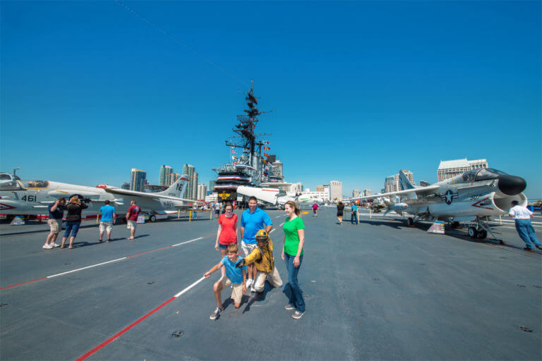 The deck of the U.S.S. Midway Aircraft Carrier which has several military aircraft parked on top of it, several visitors to the ship walking around sightseeing and the buildings of downtown San Diego peering out in the distance