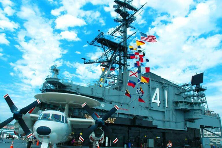 A twin engine navy prop plane parked next to the flag bridge, adorned with different colorful flags and the primary flight control area which has several observation decks in San Diego