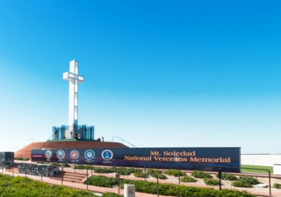 San Diego's Mount Soledad National Veterans Memorial with a long wall where all 5 logos of the military branches are displayed along with a tall white crucifix mounted at the site's highest point