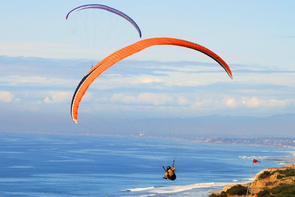 Two hang gliders soaring high above the Pacific Ocean in Torrey Pines, San Diego