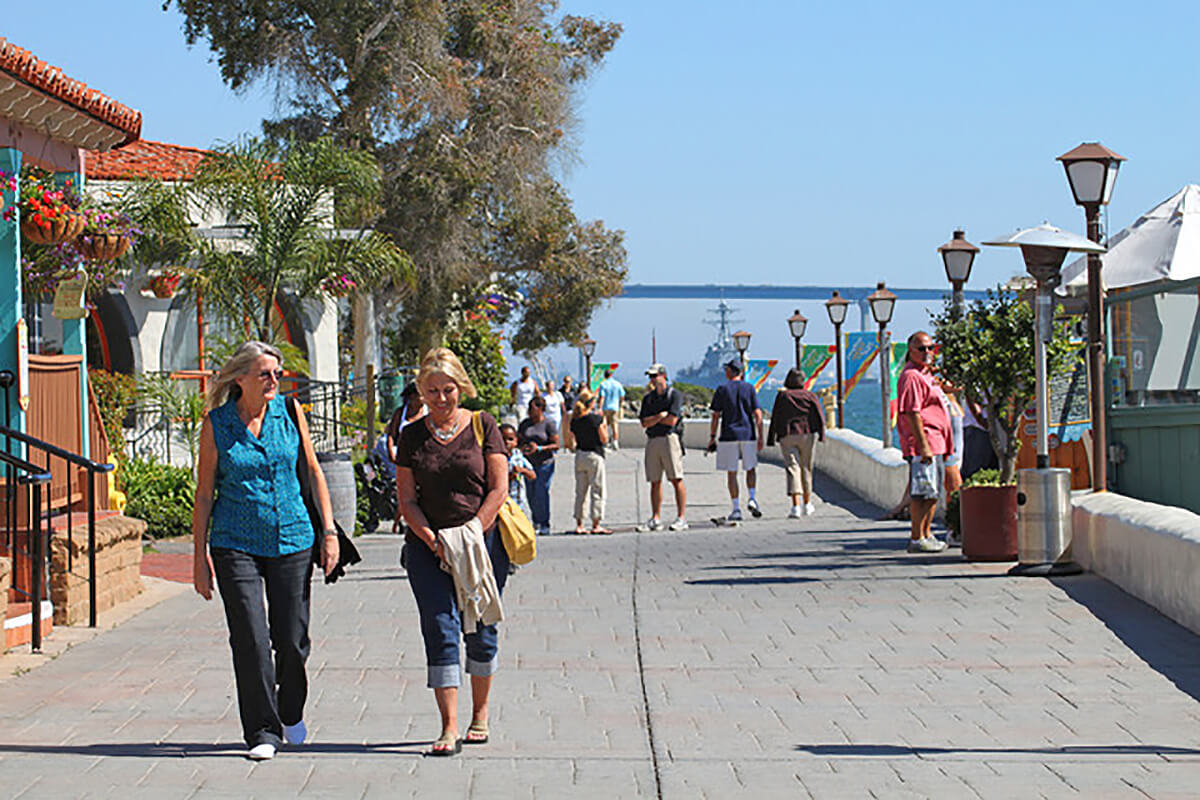 People walking up and down the boardwalk in Seaport Village San Diego with the ocean to the right and shops to the left