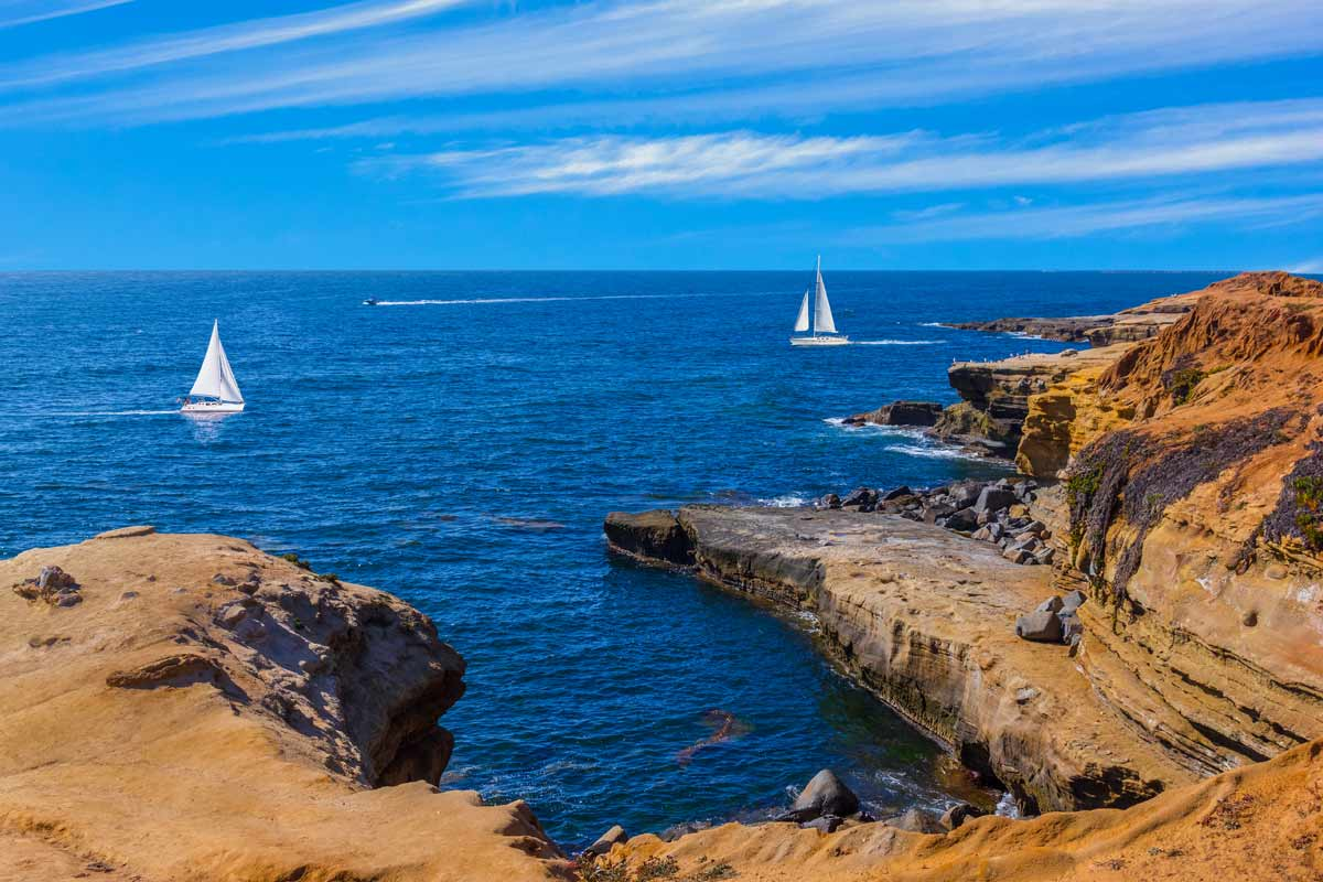 picture of cliffs in the foreground and two sailboats sailing on the ocean in the background