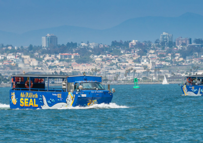 two seal tour vehicles cruise san diego bay with skyline of san diego in the background