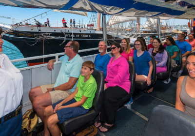 inside of seal tour vehicle showing tour guide speaking to two rows of guests while vehicle is on the water and the star of india tall ship is on the left